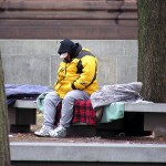 Homeless man sitting on bench with sleeping back